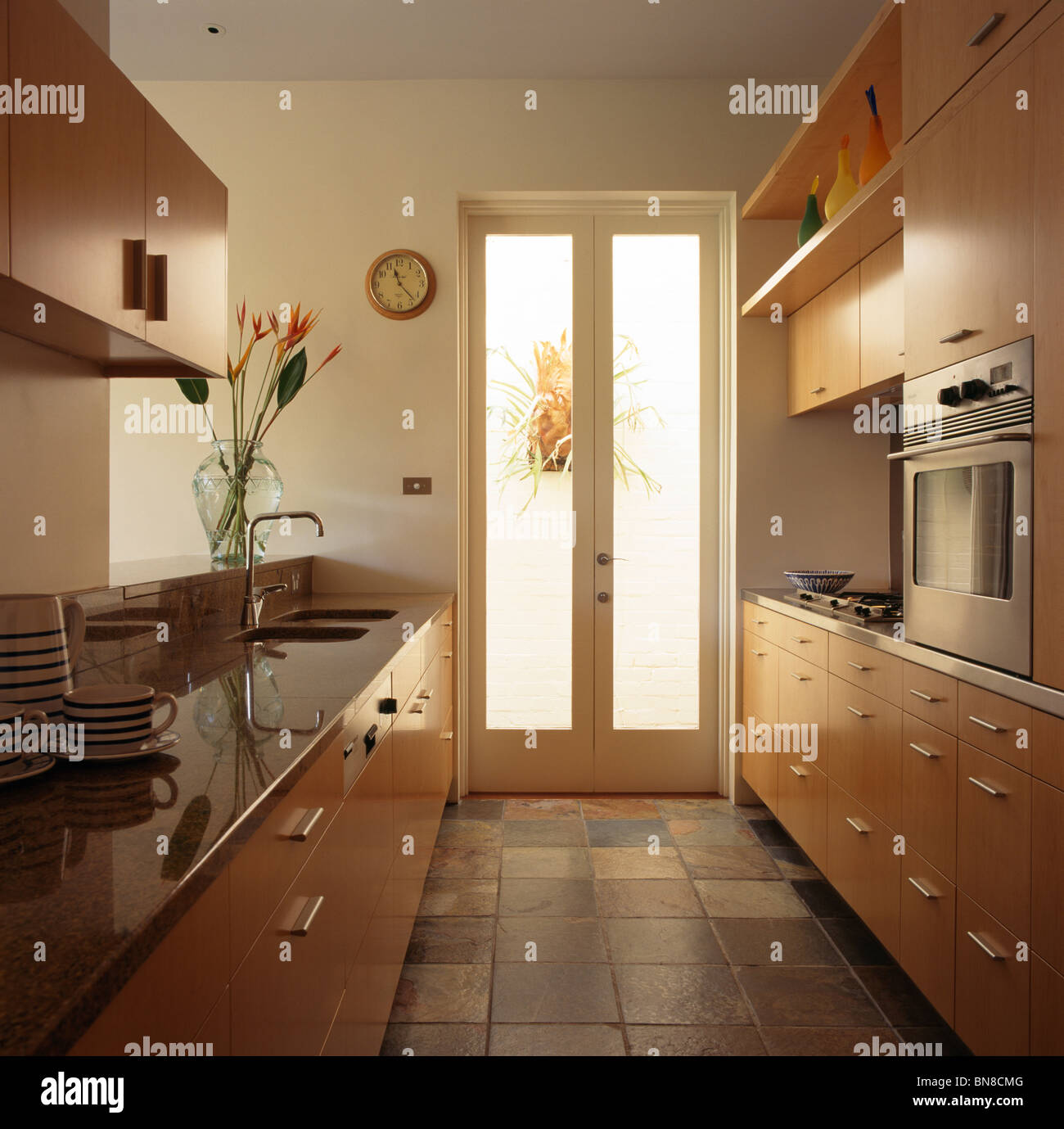 Slate floor tiles and glass double doors in galley kitchen with pale ...