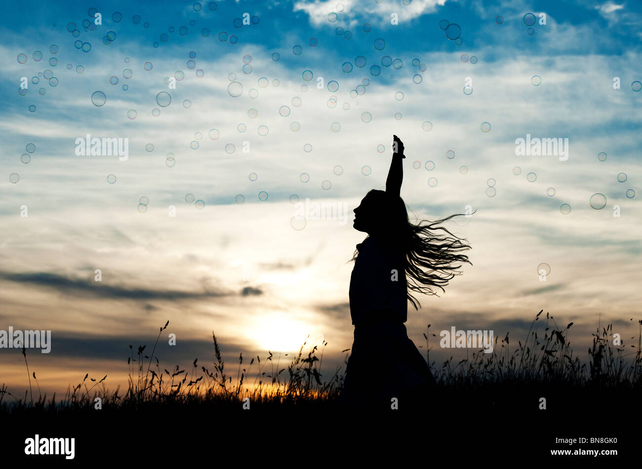 Young Girl energetically having fun jumping and catching bubbles at sunset. Silhouette Stock Photo