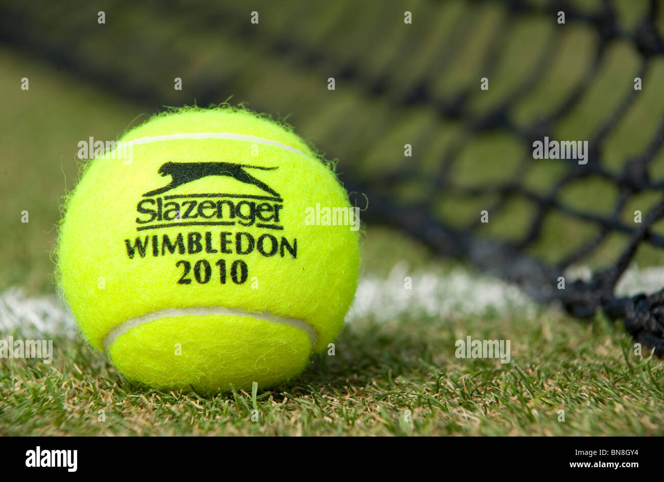 Wimbledon 2010 Slazenger tennis ball sits on a grass court during the Wimbledon Tennis Championships 2010  - Stock Image