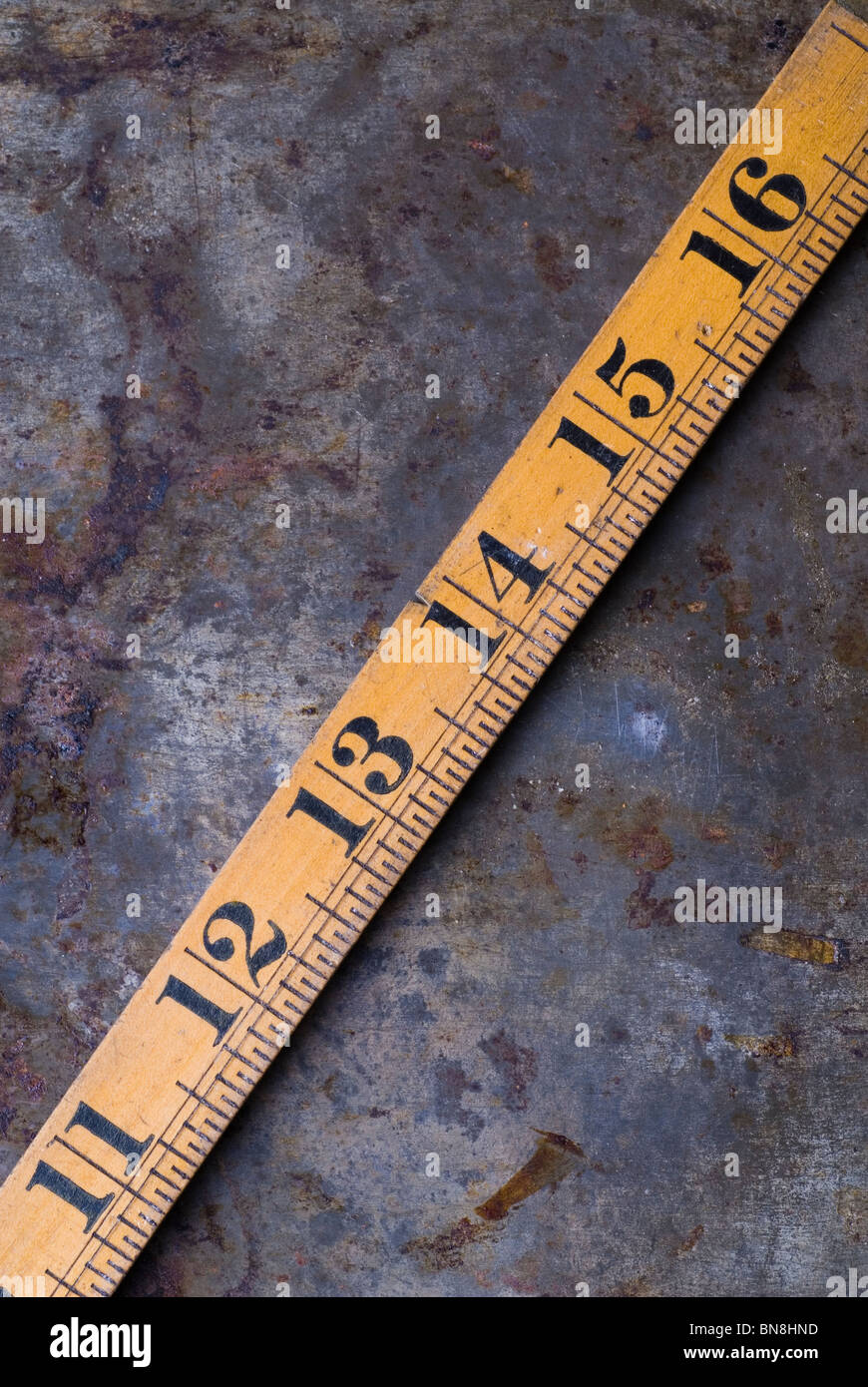 Old wooden ruler over a rusty grunge background - Stock Image