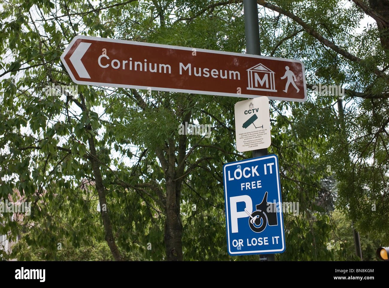 Signs in town car park showing direction to museum and warning of theft to motorcyclists - Stock Image