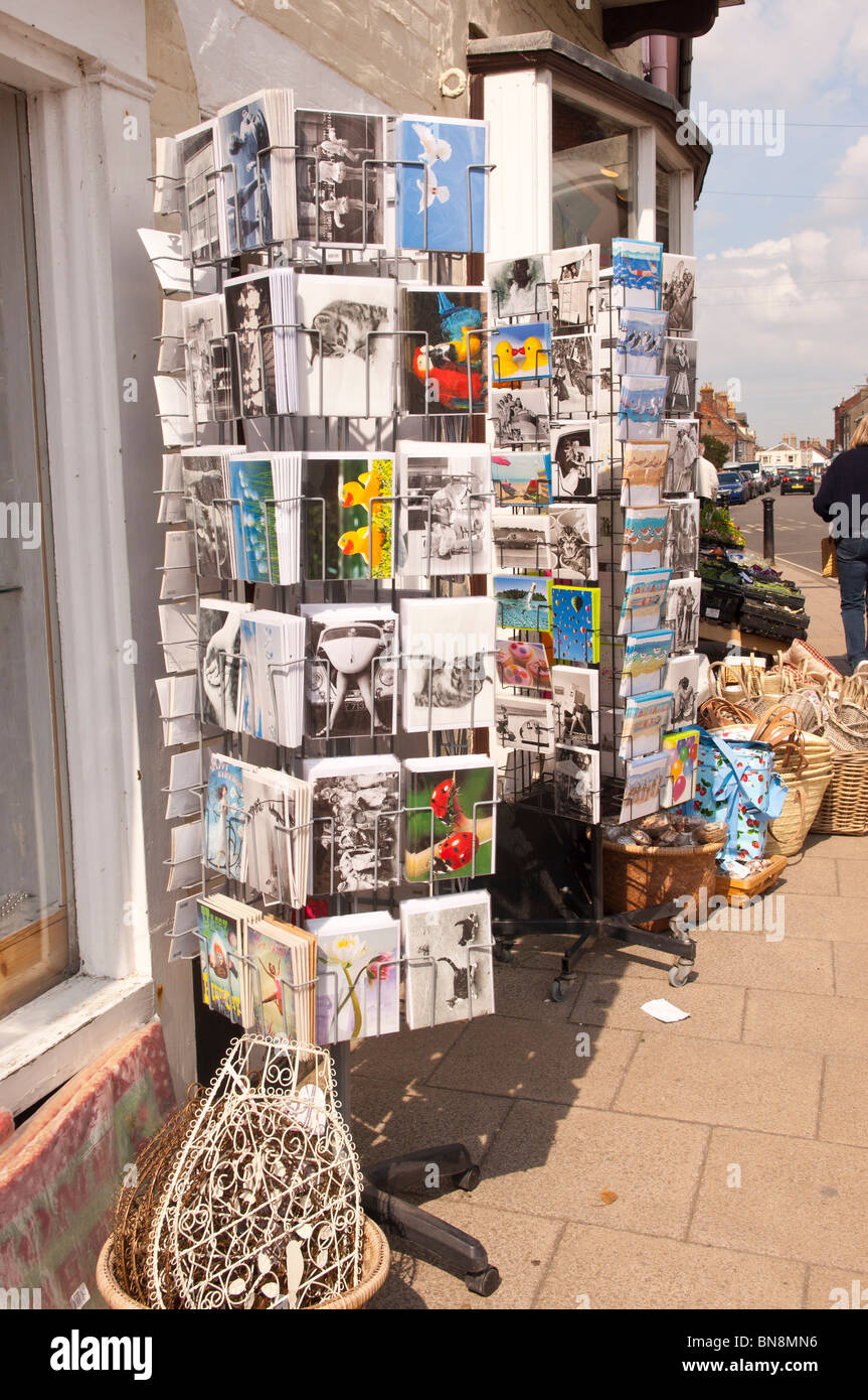 Postcards for sale on a stand outside a shop store at Southwold , Suffolk , England , Great Britain , Uk - Stock Image