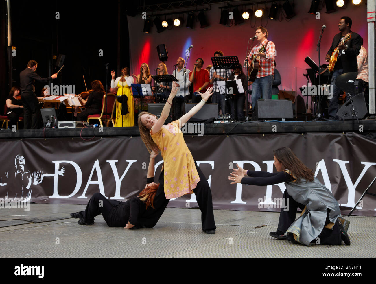 Dave Bilbrough singing on stage and MiW dancers at the 2010 London Global Day of Prayer. - Stock Image