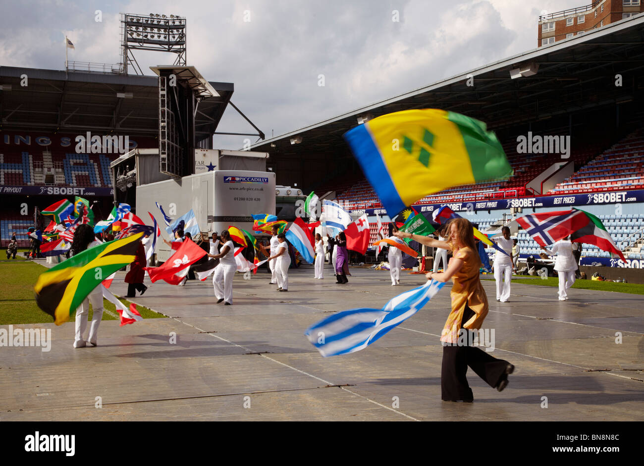 Dancers with national flags at the 2010 London Global Day of Prayer. West Ham United Football Club, Upton Park, - Stock Image