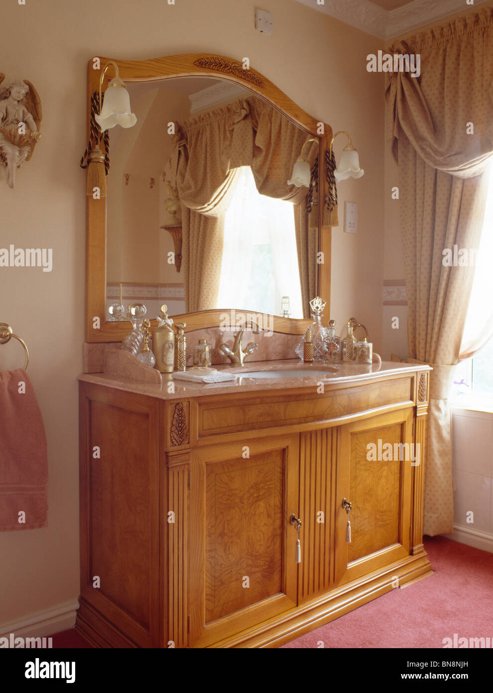 Large mirror above pale wood vanity unit in traditional bathroom - Stock Image