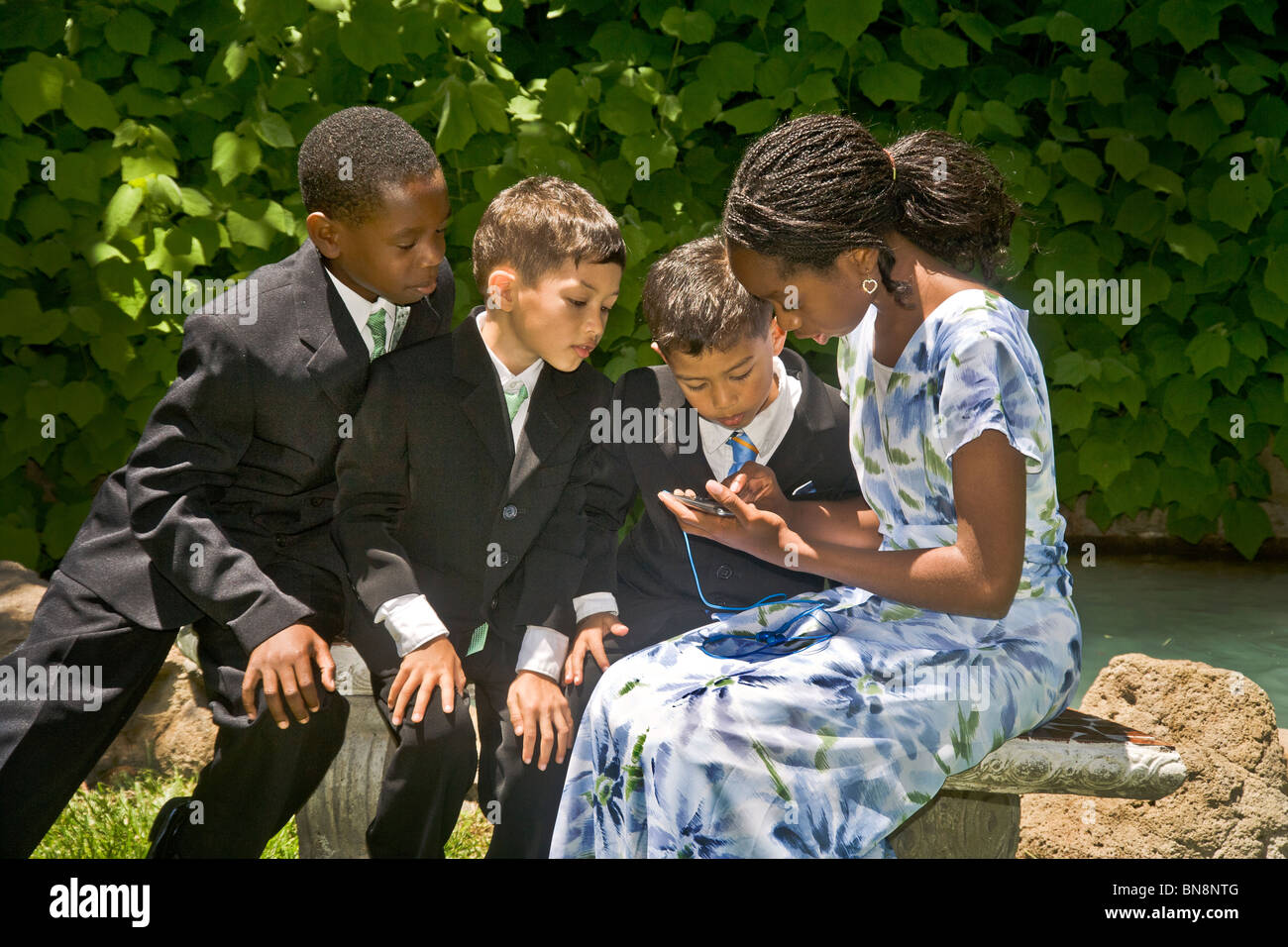 Multiracial young guests are fascinated by an IPhone before a formal outdoor wedding in Orange, CA. - Stock Image