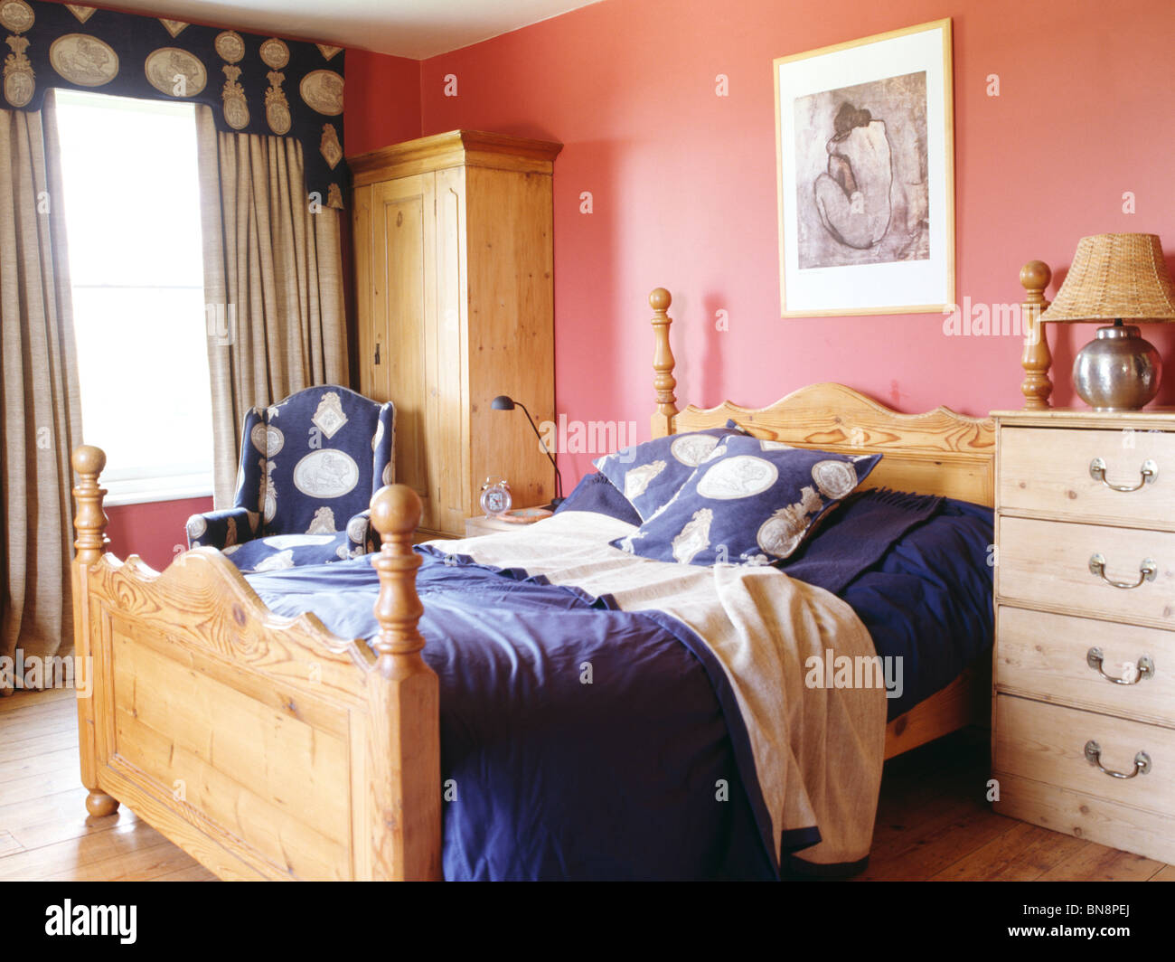 Pine bed with blue cushions and bedlinen in pink bedroom with pine ...