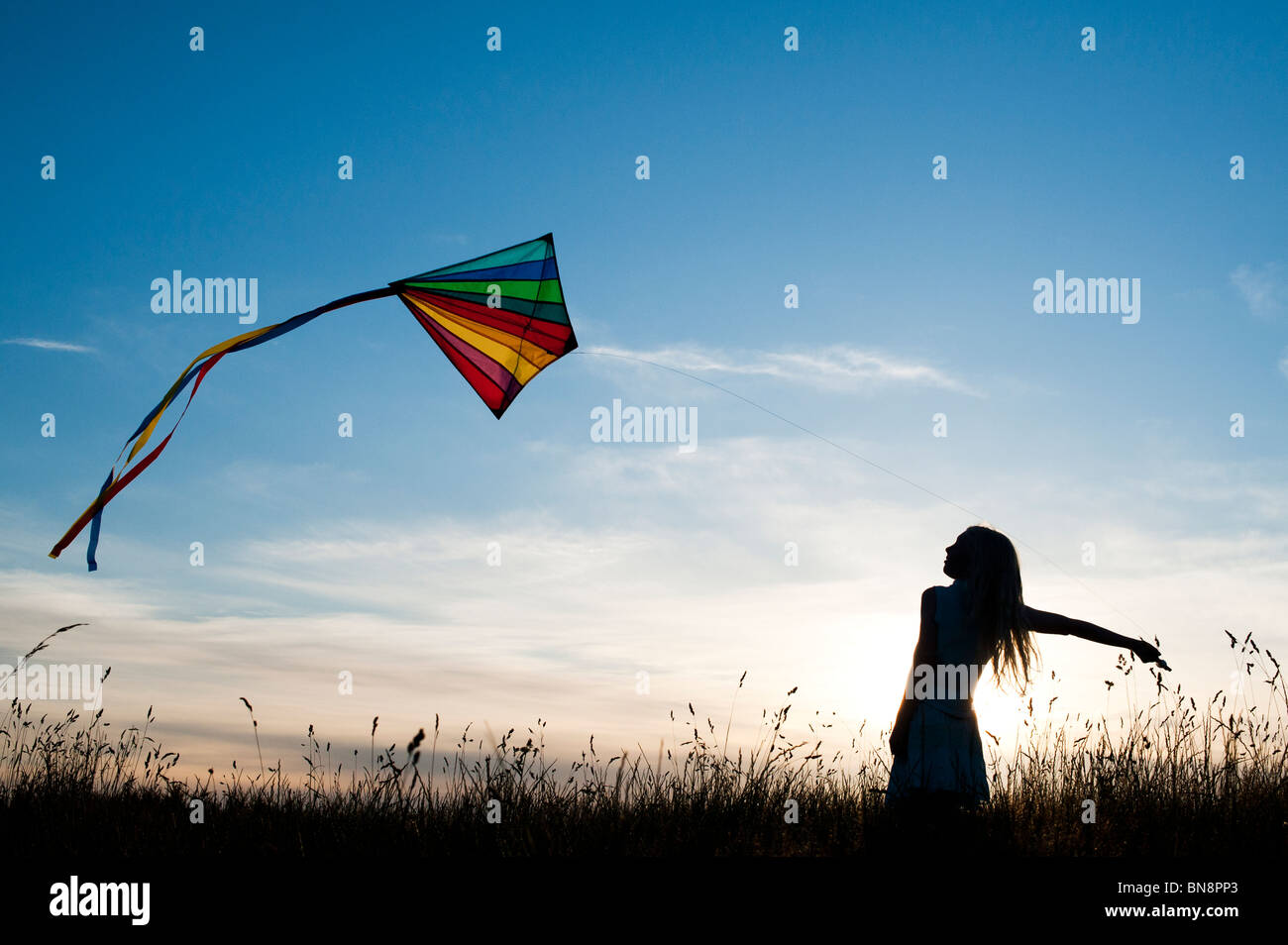 Young Girl having fun flying a multicoloured kite in the English countryside. Silhouette Stock Photo