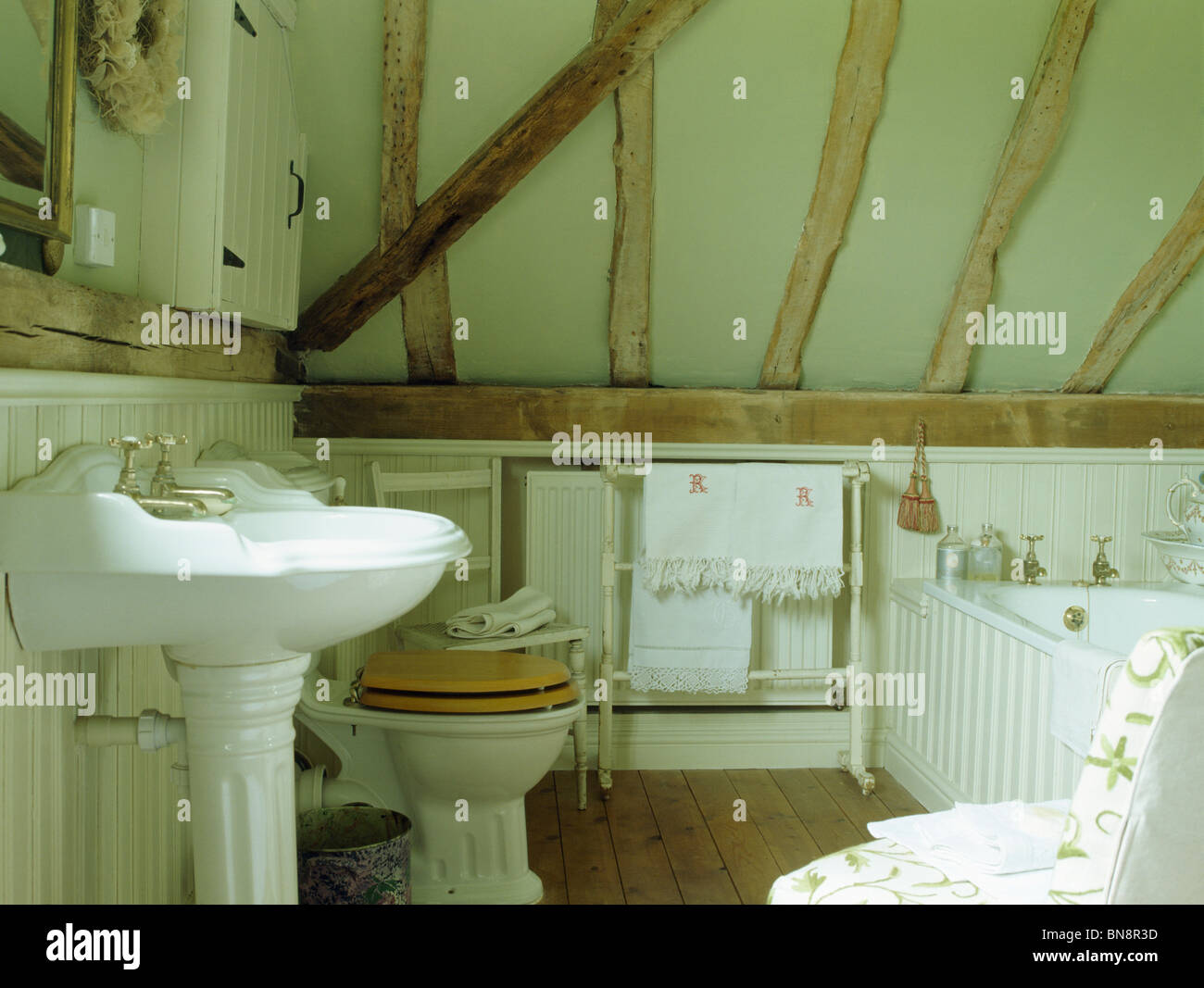 White pedestal basin in bathroom with low beamed ceiling Stock Photo ...
