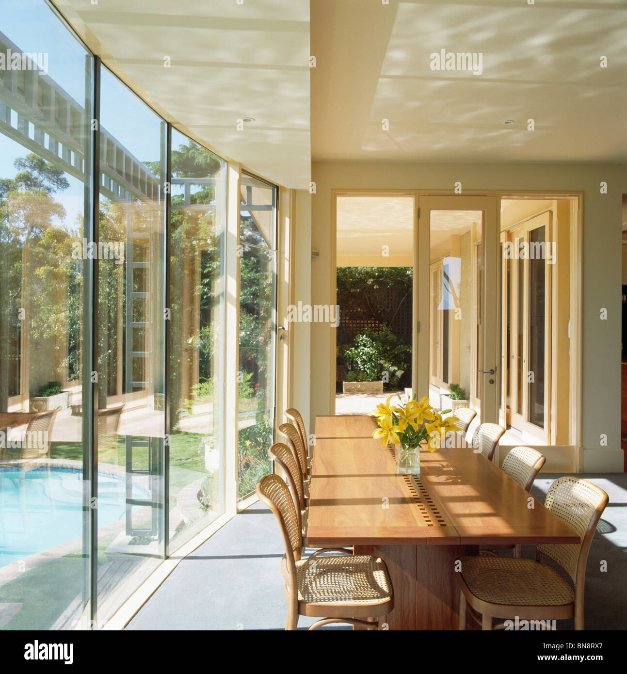 Wooden Table In Large Modern Dining Room Extension With Glass Wall And View Of Swimming Pool