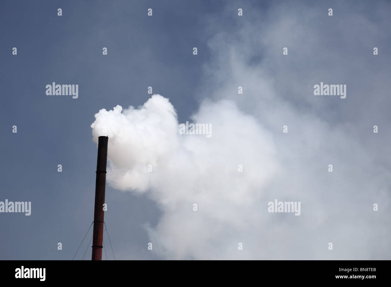 Factory chimney blowing co2 into atmosphere - Stock Image