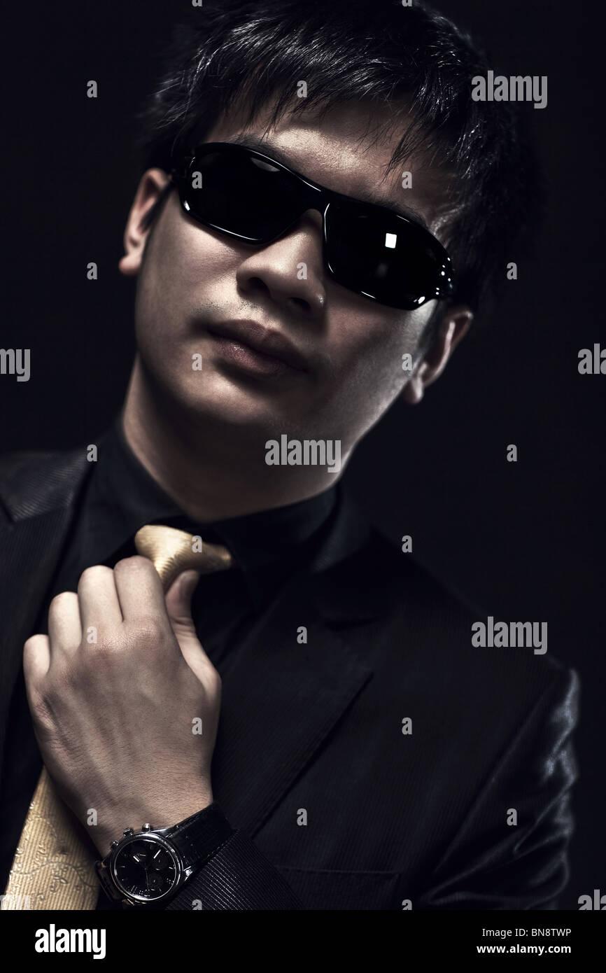 Cool japanese man in sunglasses portrait. Dark colors. - Stock Image