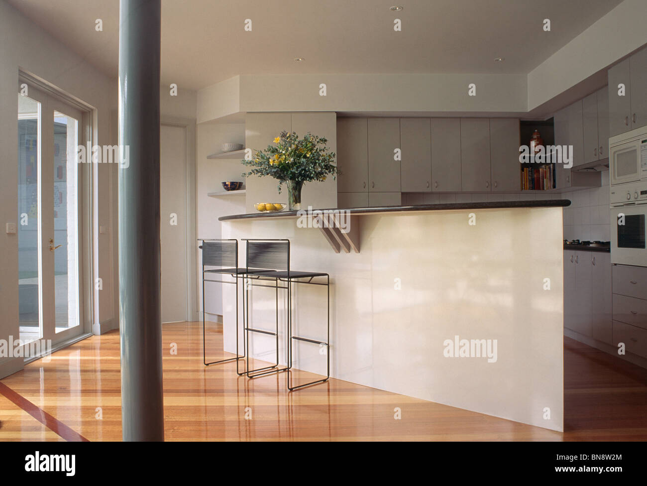 open plan kitchen breakfast bar. Narrow pillar and wooden flooring in modern open plan kitchen with stools  at breakfast bar