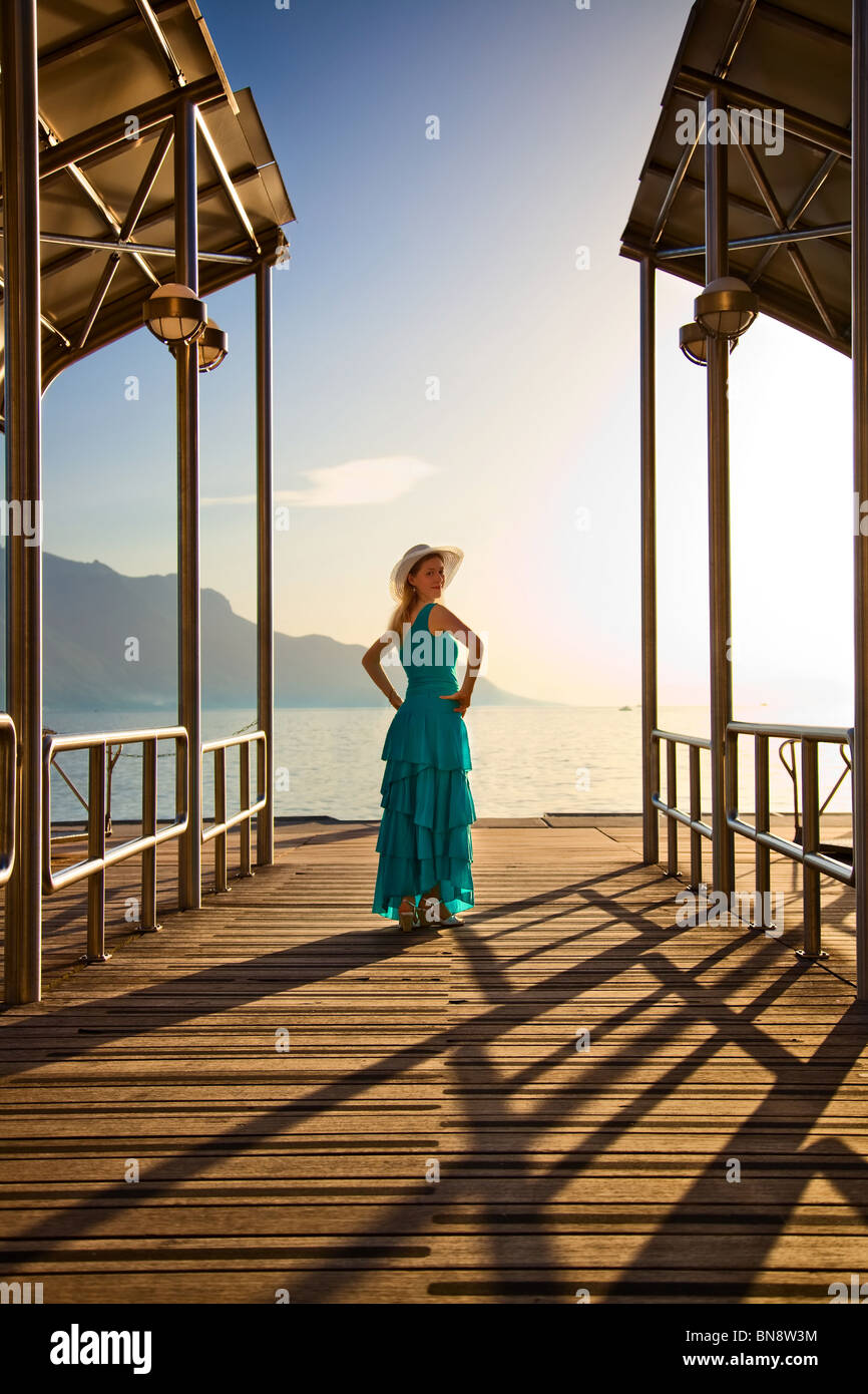 Young woman in blue dress standing at the moorage. - Stock Image