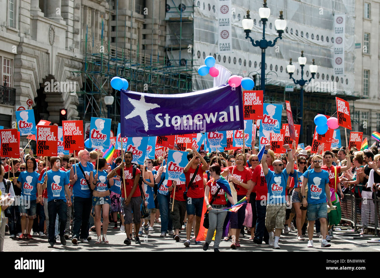 Participants holding placards and a Stonewall banner during the Pride London celebrations. - Stock Image