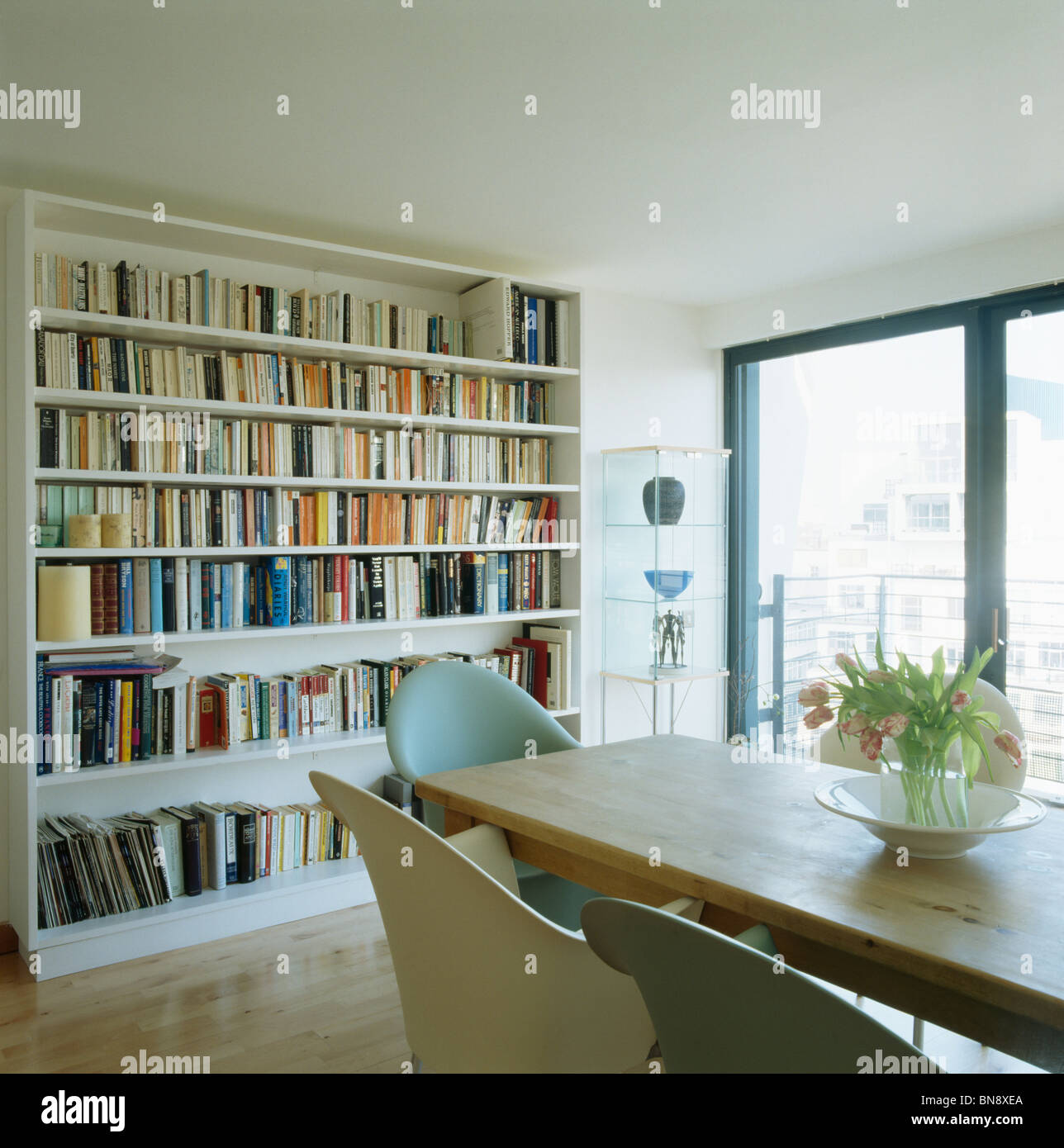 Wall Of Bookshelves In Modern White Dining Room With Wooden Table Stock Photo Alamy