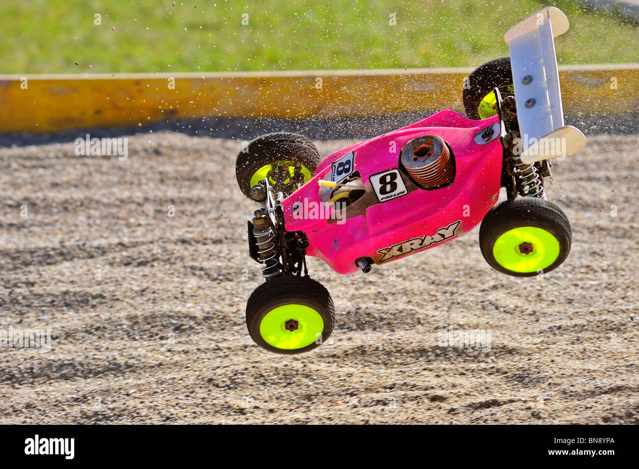 Radio-controlled buggy, racing in the European championships, caught in mid-air at a jump on the course. - Stock Image