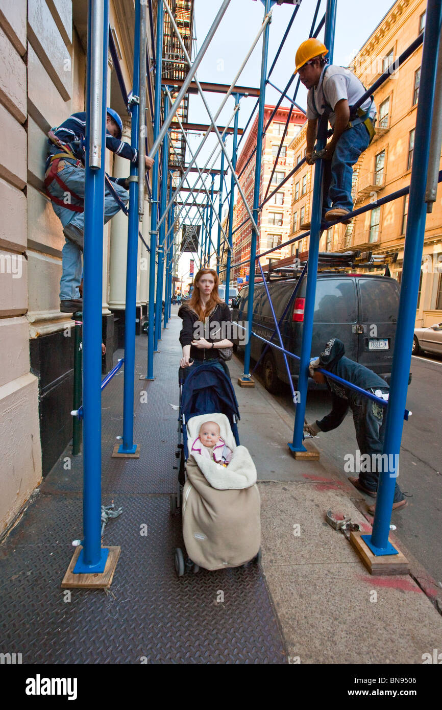 Woman with baby stroller, men assembling scaffolding, Tribeca, New York Stock Photo
