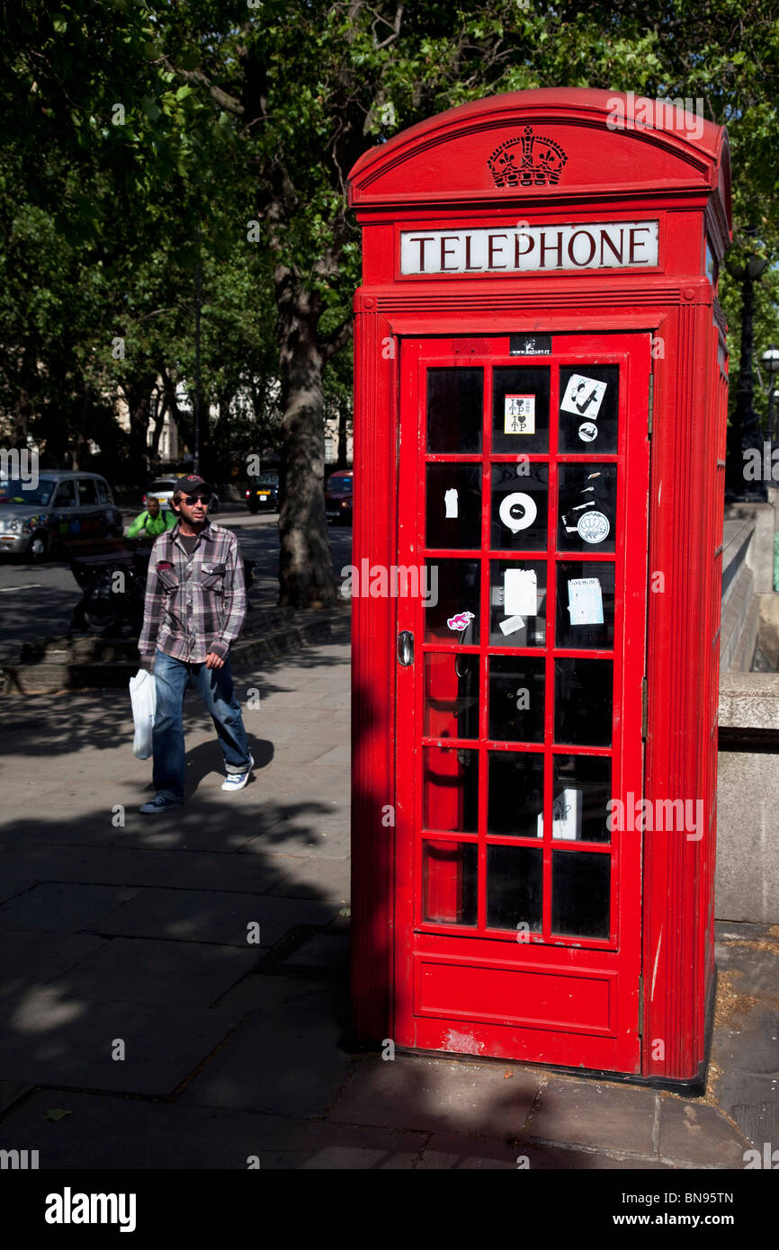 The red telephone box, a public telephone kiosk designed by Sir Giles Gilbert Scott, a familiar sight on the streets - Stock Image