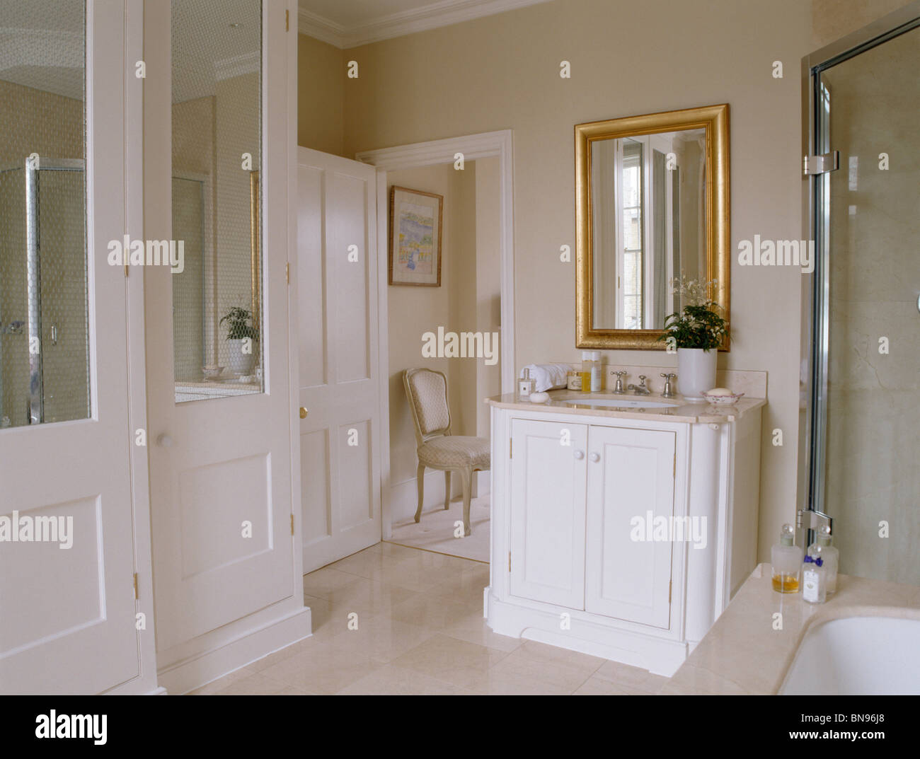 Gilt mirror above vanity unit in traditional cream townhouse bathroom - Stock Image