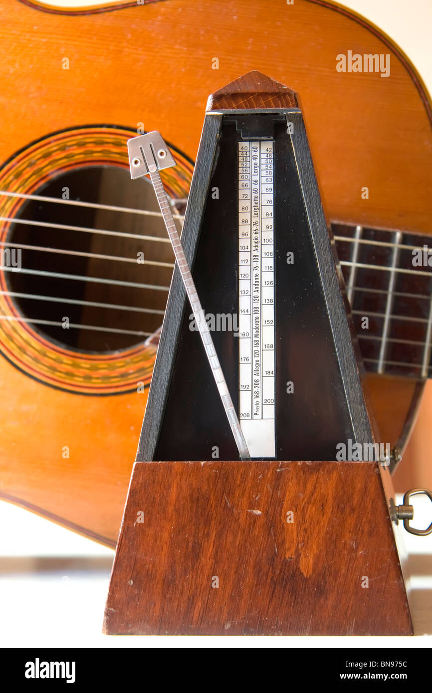 Metronome with a guitar behind - Stock Image