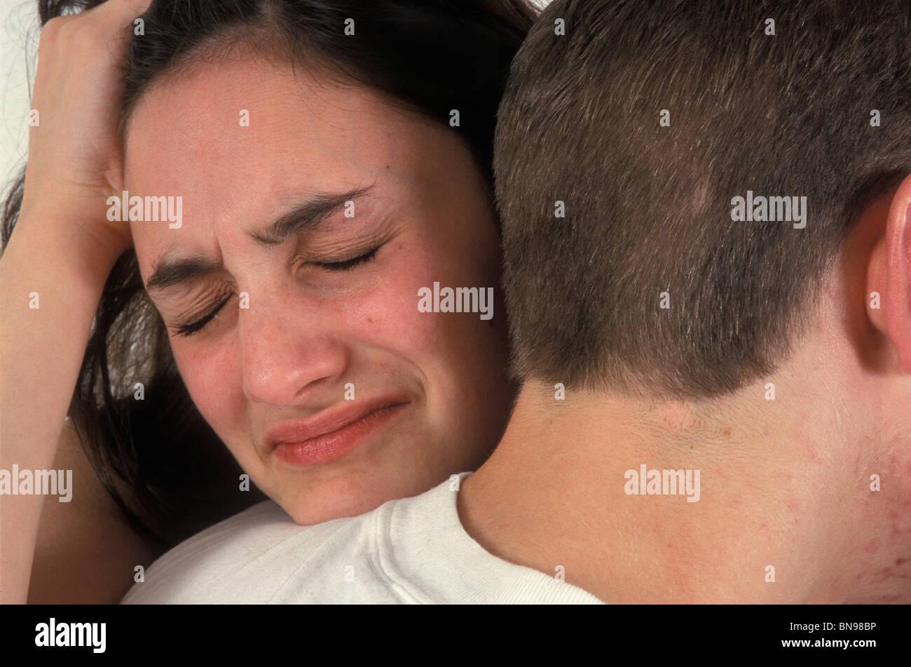 Distressed teenage girl clinging onto boyfriend - Stock Image
