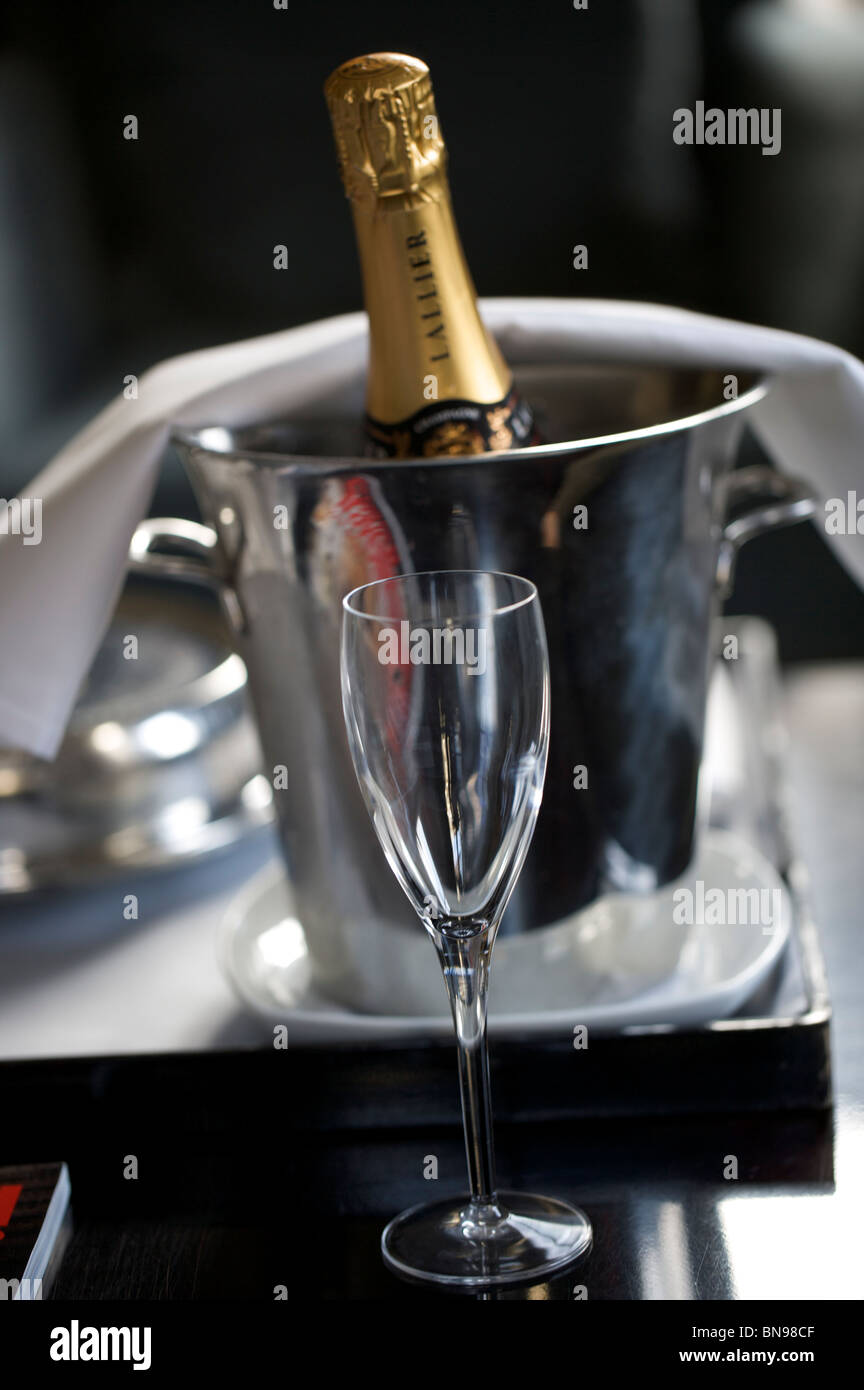 Champagne bottle in ice bucket with glass - Stock Image
