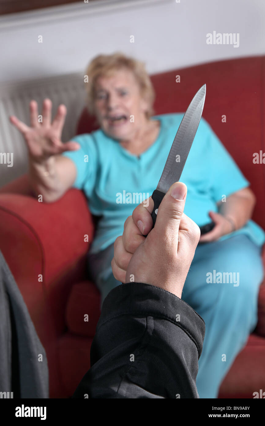 Knife pulled as terrified elderly woman looks towards the attacker - Stock Image