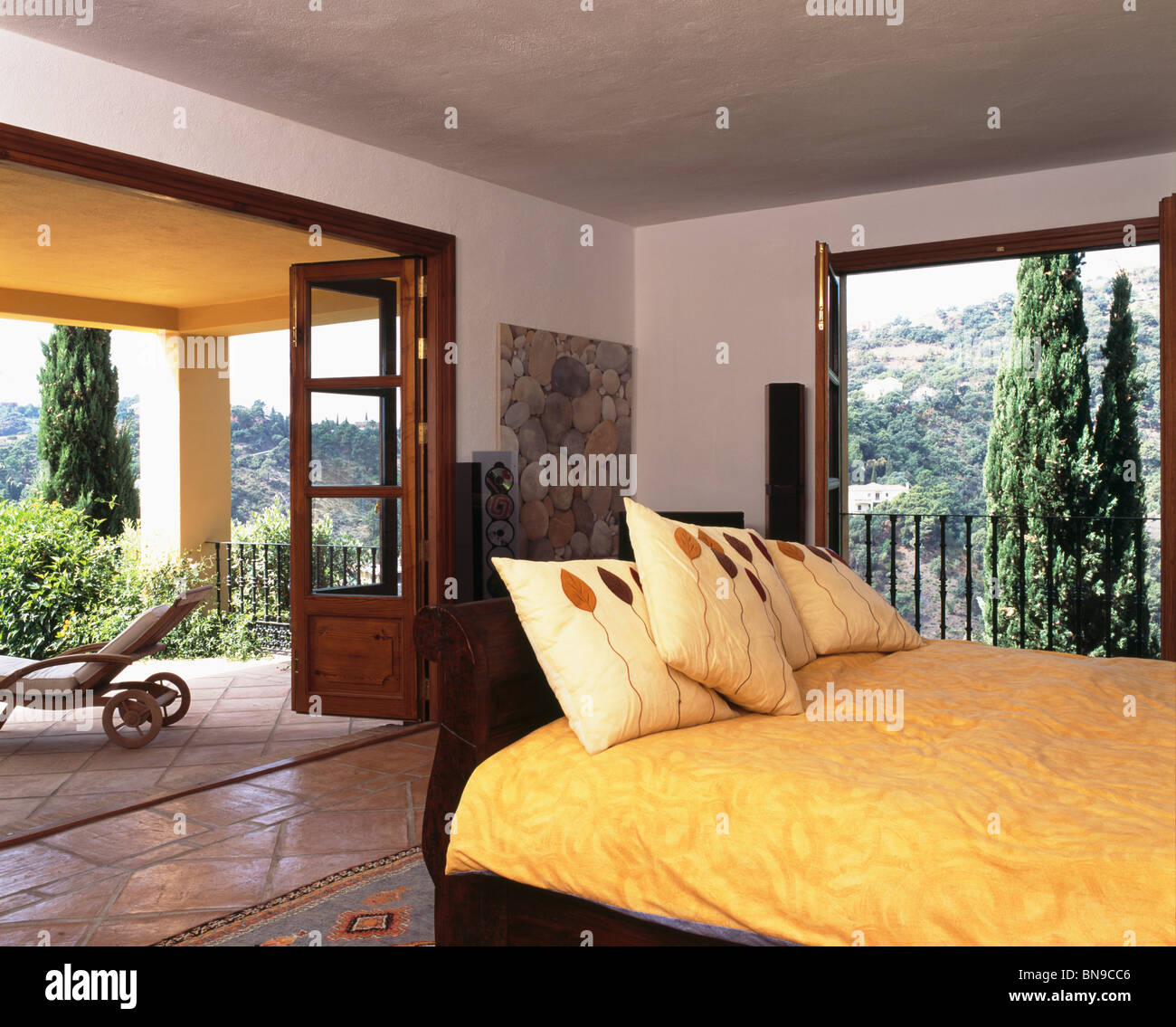 Yellow Cushions And Quilt On Bed In Modern Spanish Bedroom With Large Patio  Doors To Veranda