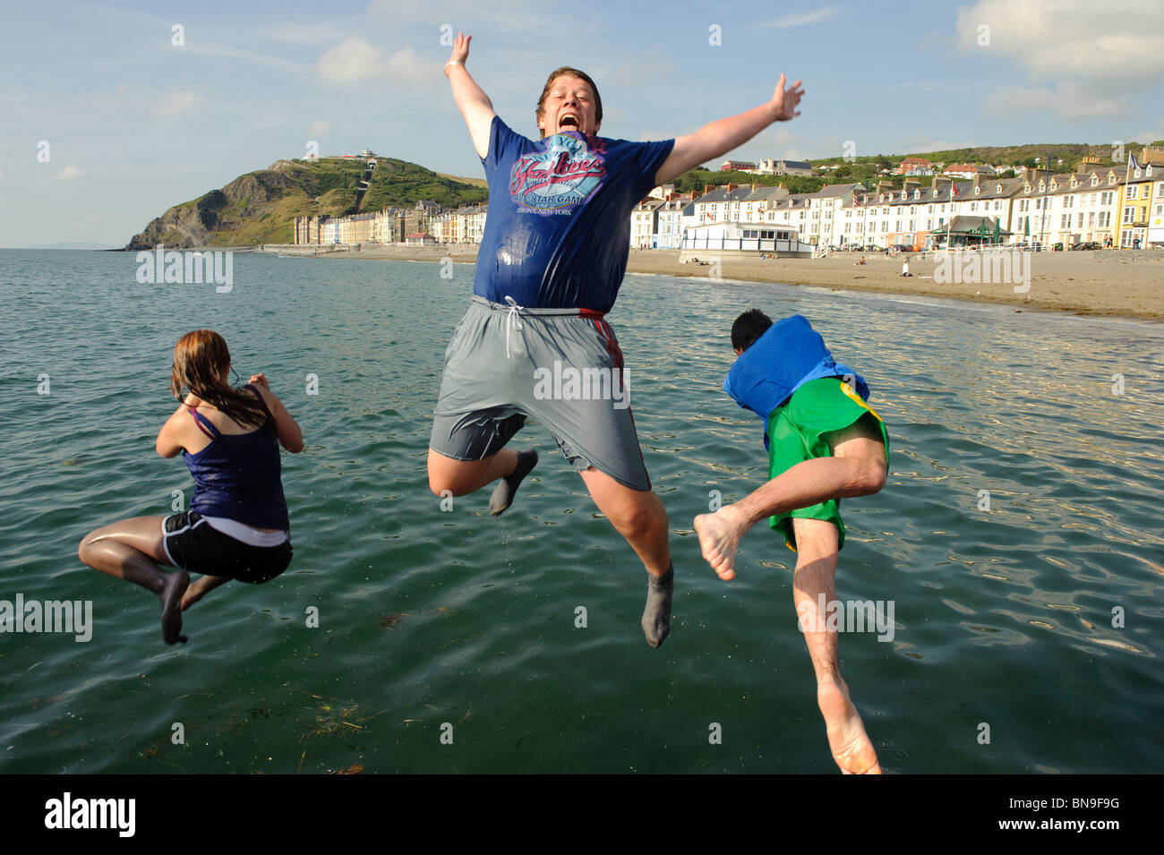 Three Teenagers jumping into the sea off the jetty on the beach at Aberystwyth Wales UK on a hot day in summer, - Stock Image