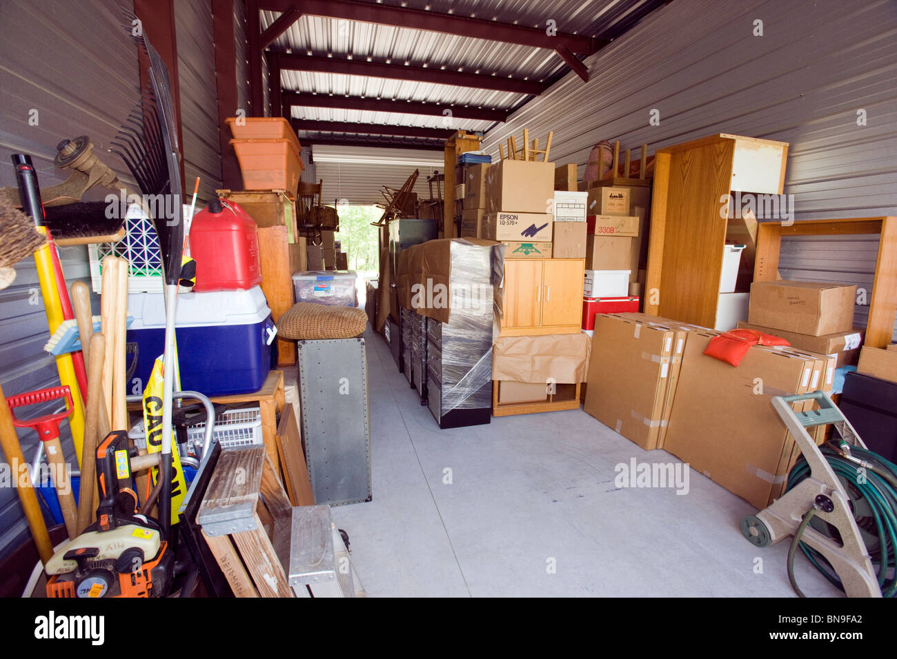 Family personal house hold belongings temporarily stored in a mini storage facility. - Stock Image