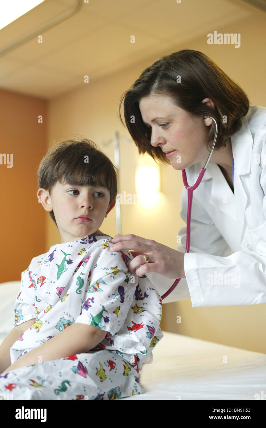female doctor giving young boy an exam - Stock Image