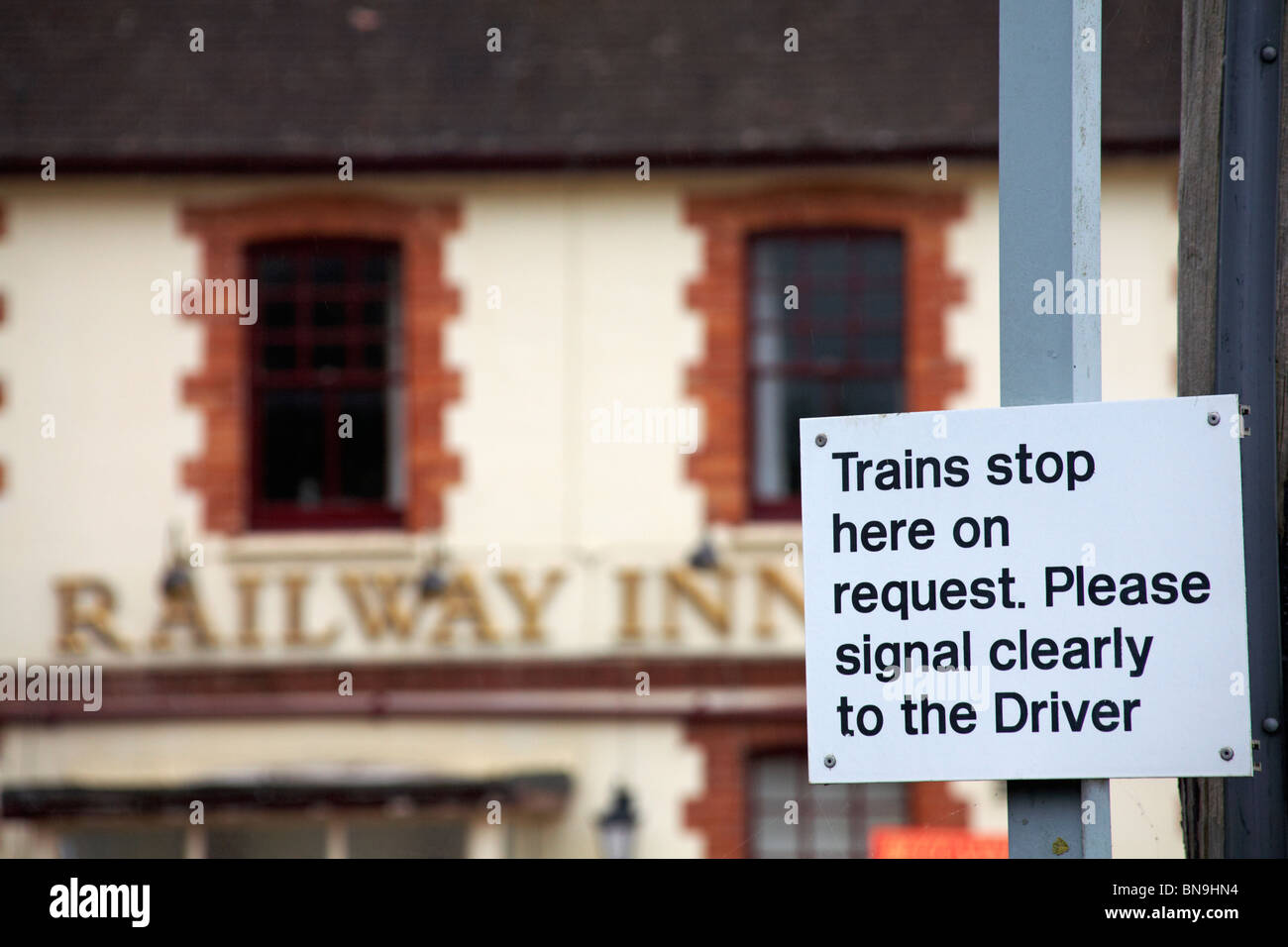 Trains stop here on request. Please signal clearly to the driver sign at Yetminster station with out of focus Railway - Stock Image