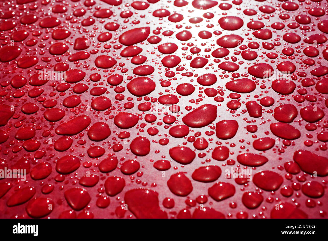 Close up macro photograph of rain drops on a red table Stock Photo