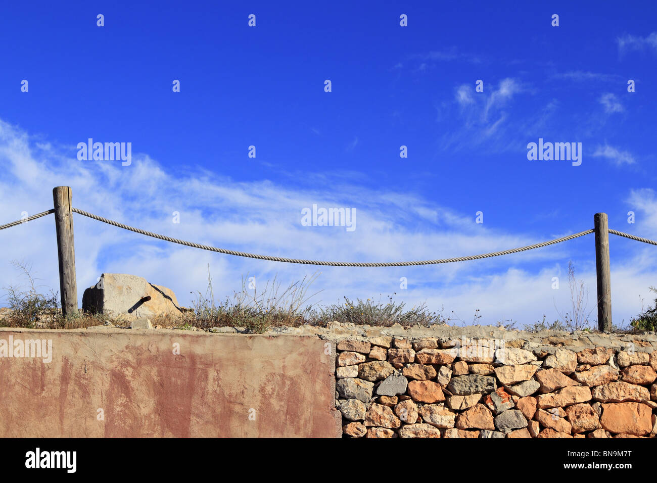 traditional rope fence over stone wall grunge cement blue sky - Stock Image