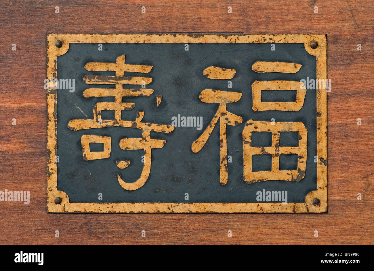 Old metal sign on wood with Chinese Characters that mean longevity, happiness and long life. - Stock Image