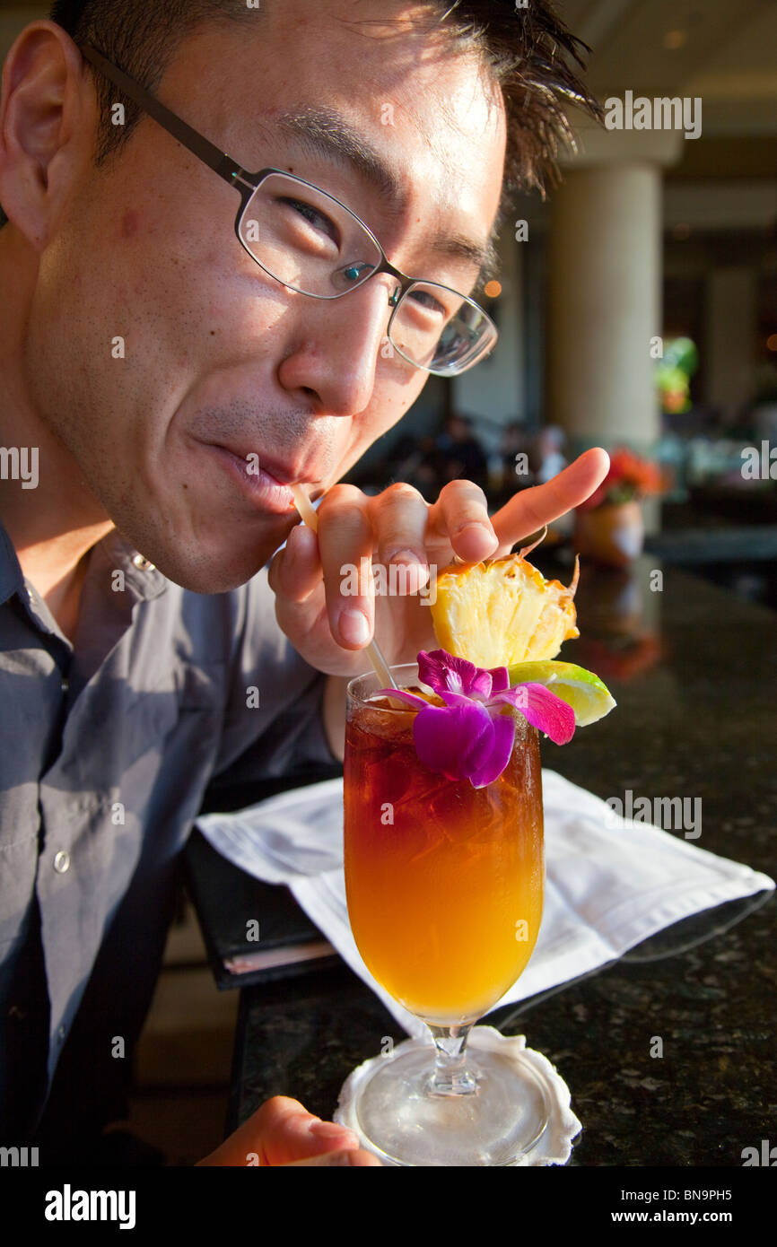 Korean American tourist enjoying a Mai Tai Tropical Drink at Four Seasons Resort in Maui, Hawaii - Stock Image