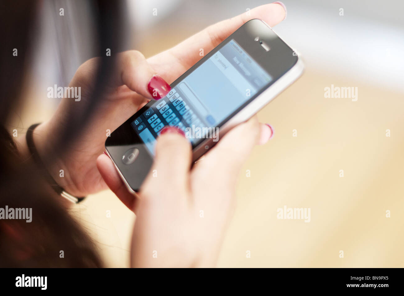 Girl texting on apple I phone 4 smart phone-close-up - Stock Image