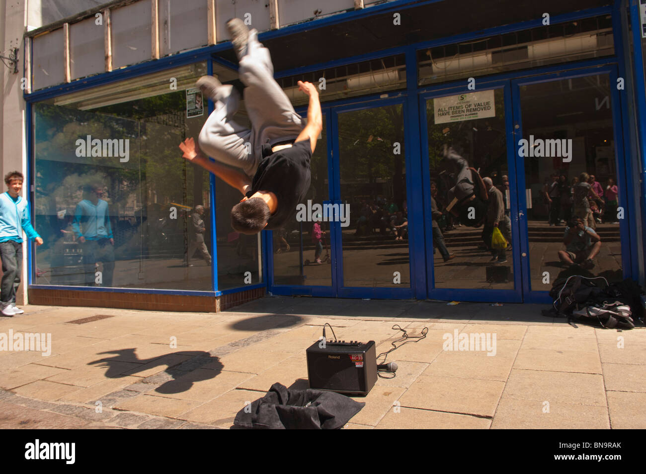 A Free Runner busking and showing movement in the streets of Norwich , Norfolk , England , Great Britain , Uk - Stock Image