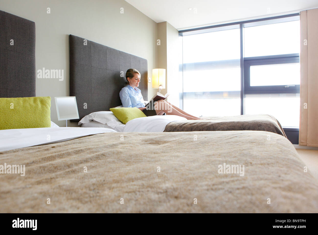 Woman reading a book sitting on a bed in an apartment, - Stock Image