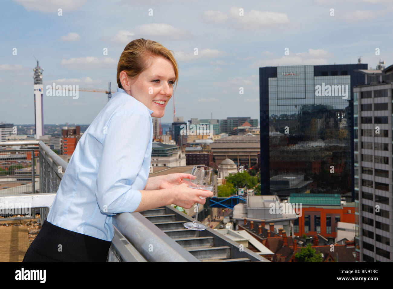 Women looking out at the city from her apartment in Birmingham. - Stock Image