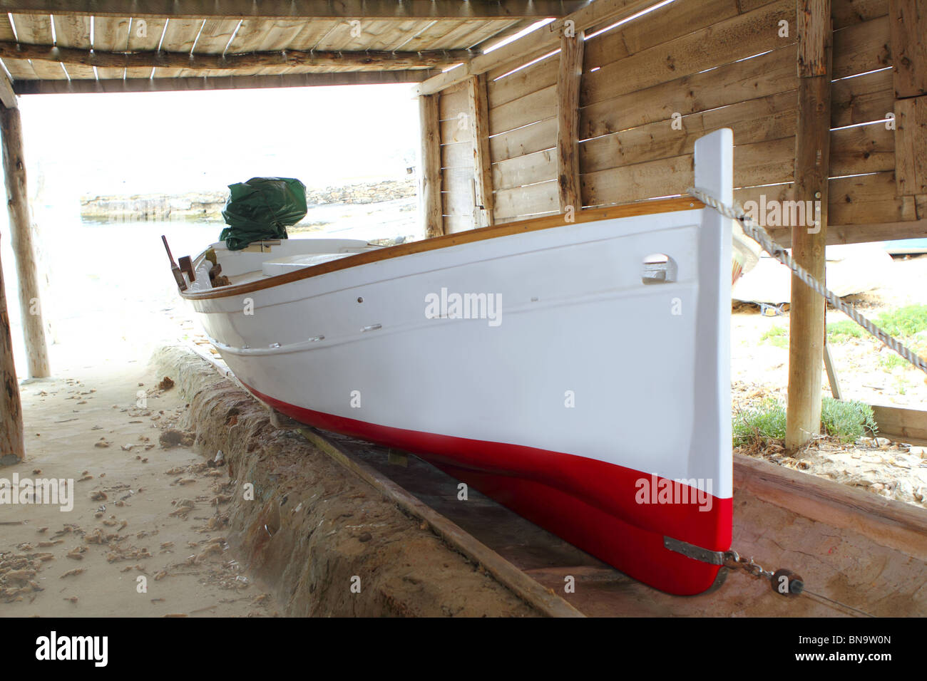 Formentera traditional boat stranded on wooden rails - Stock Image