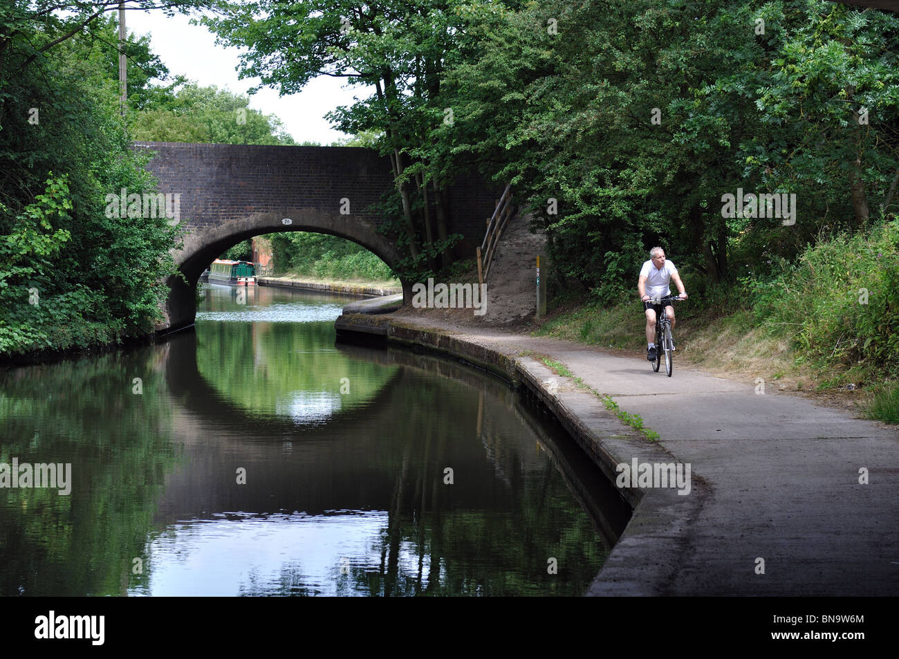 Cyclist on Grand Union Canal towpath, Copt Heath, West Midlands, England, UK - Stock Image
