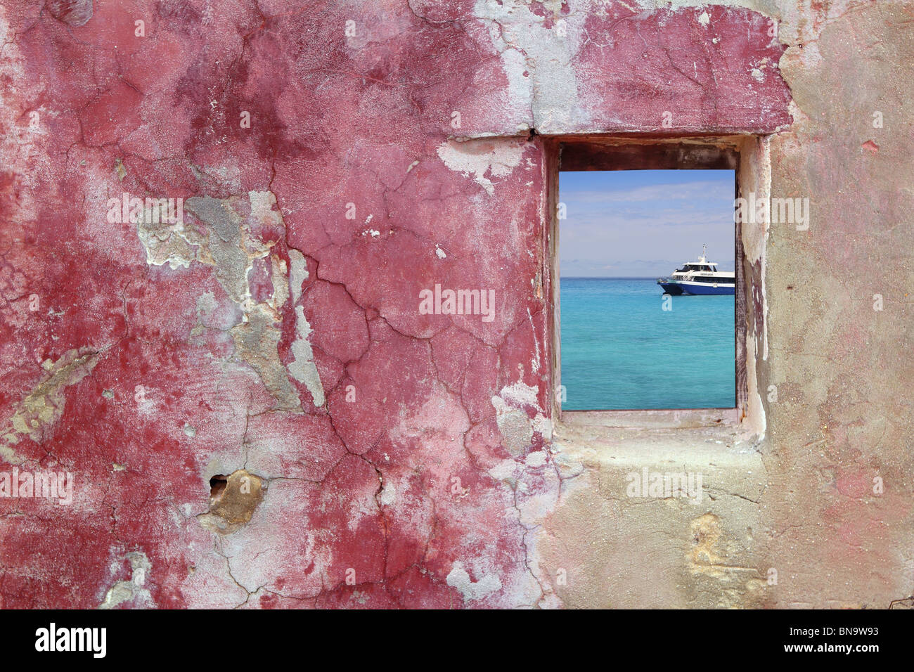 grunge pink red wall wood window tropical turquoise sea boat view - Stock Image
