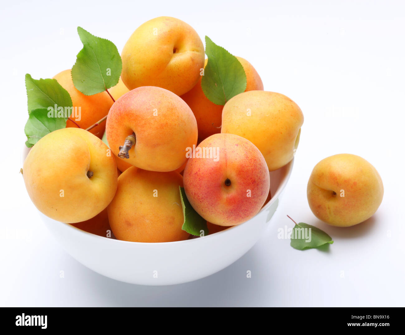 Crockery with mellow apricots. Isolated on a white background. - Stock Image
