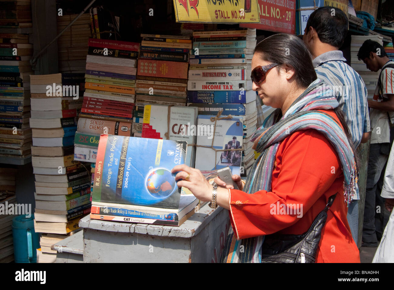 A lady browses through a book at a shop on College Street in Kolkata (Calcutta), West Bengal, India. - Stock Image