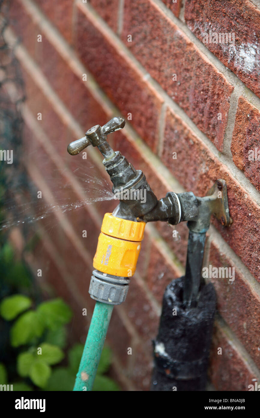 An outside leaking tap causing water shortage which could lead to a hosepipe ban - Stock Image