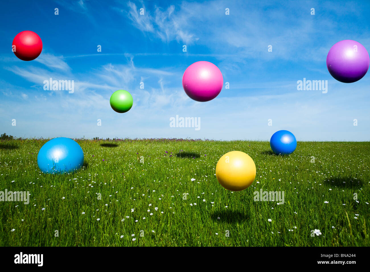 Colored balls jumping on a green meadow - Stock Image