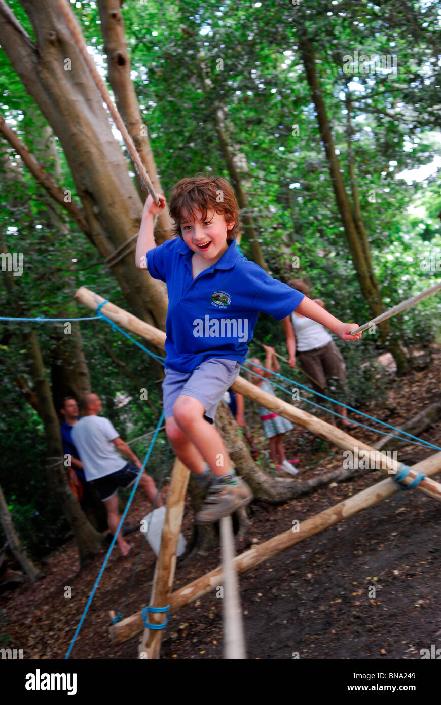 7 year old boy negotiating the monkeybridge (tightrope) course at a scouts centenary celebration day, Haslemere, - Stock Image