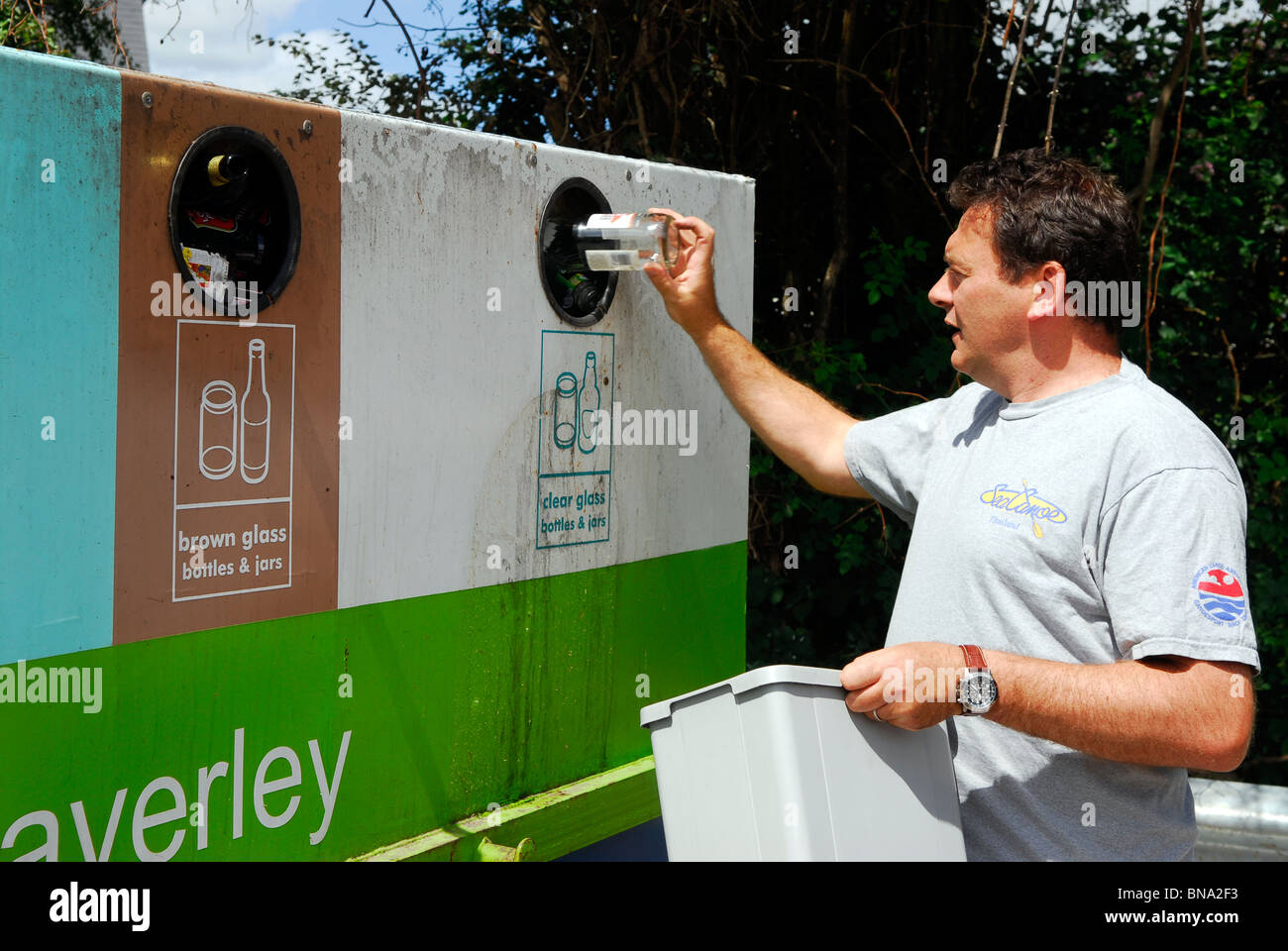 Man placing bottle in bottle bank for recycling, Wey Hill, Haslemere, Surrey, UK. - Stock Image